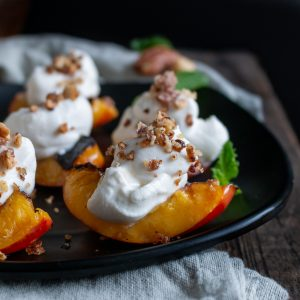Grilled Nectarines with Coconut Cream on a black plate garnished with crushed nuts and mint leaves.