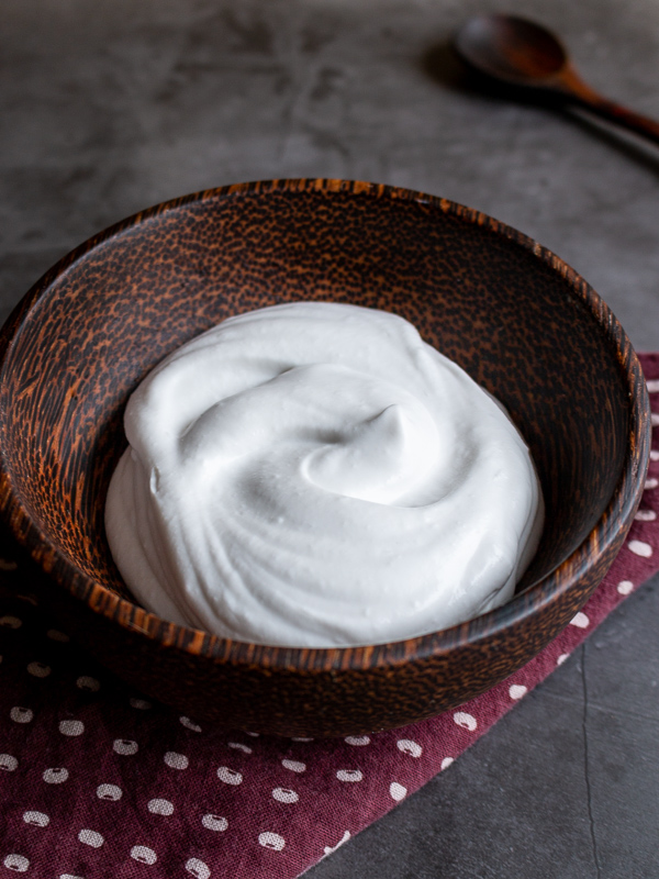 Homemade Coconut Whipped Cream in a brown wooden bowl.
