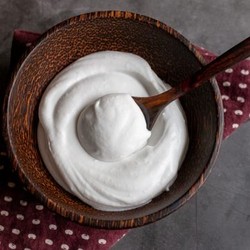 Top down photo of creamy dreamy coconut whipped topping in a brown wooden bowl with a dollop in a wooden spoon.
