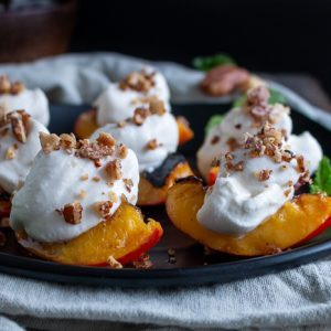 Grilled Nectarines with a dollop of whipped coconut cream and crushed candied nuts on each.