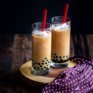 2 glasses of Homemade Cream Earl Grey Bubble Tea with red straws in tall glasses on a wooden board with a wine colored napkin.