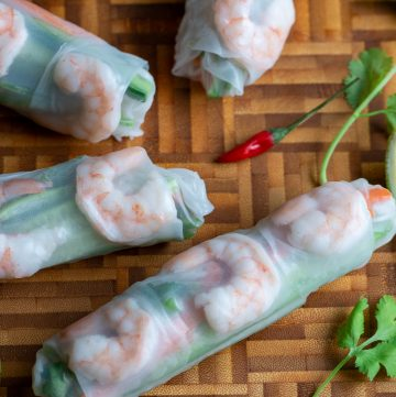 4 summer rolls with a bowl of chili lime sauce on a cutting board.