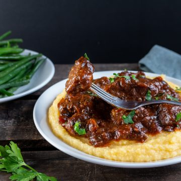 Tuscan Slow Cooked Braised Beef in Wine Sauce on a bed a creamy polenta with a bite ready for you.