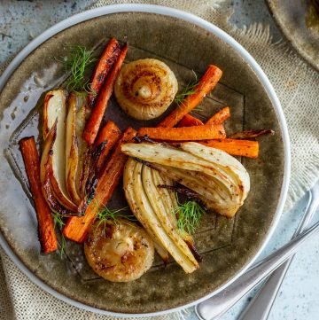 Balsamic roasted fennel, onions and carrots on a green plate with fennel as garnish.
