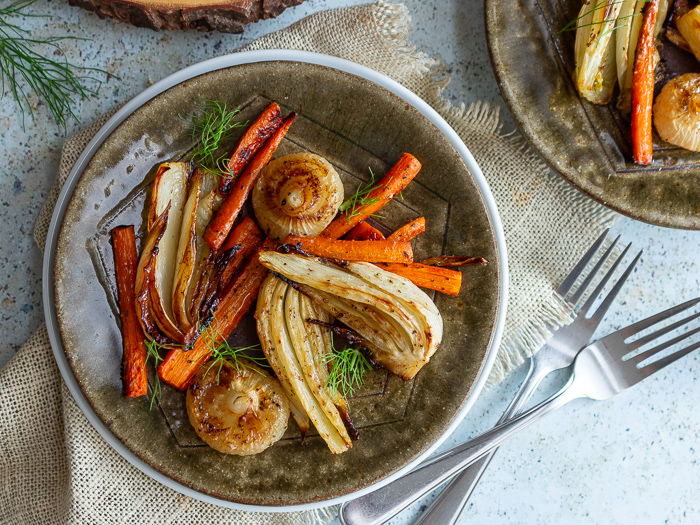 Roasted fennel, carrots and onions on a green plate garnished with green tops of fennel.