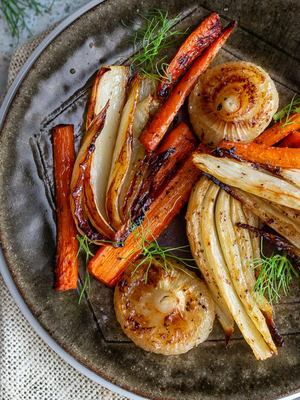 Top down shot of balsamic roasted fennel and carrots with swirly green frangs to garnish.