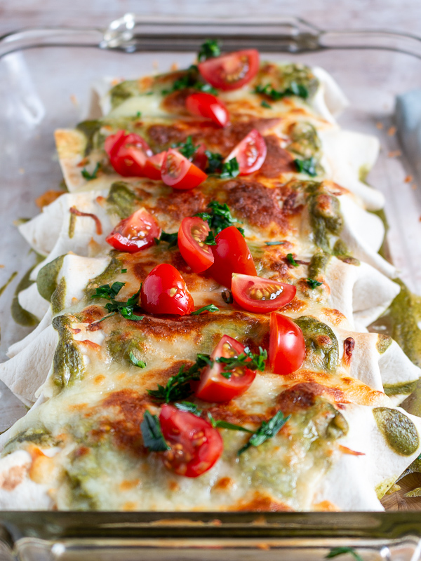 Shrimp Burritos with Creamy Poblano Sauce topped with chopped tomatoes and cilantro in a clear 9 x 13 baking dish.