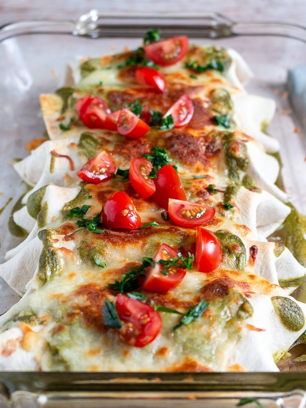 Burritos topped with chopped tomatoes and cilantro in a clear 9 x 13 baking dish.