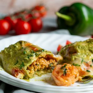 Shrimp Burritos with Creamy Poblano Sauce cut in half to show the shrimp and rice mixture on a white plate.