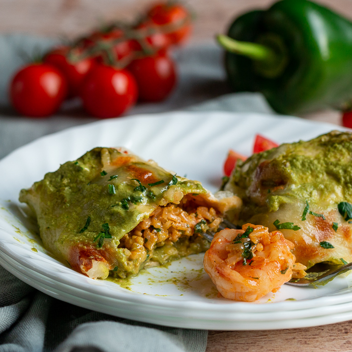 Shrimp Burritos with Creamy Poblano Sauce cut in half to show the delicious creamy rice and perfectly cooked shrimp on a white plate.