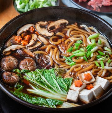 Sukiyaki Beef Udon cooking with tofu, mushroom noodles and vegetables in a black pot.