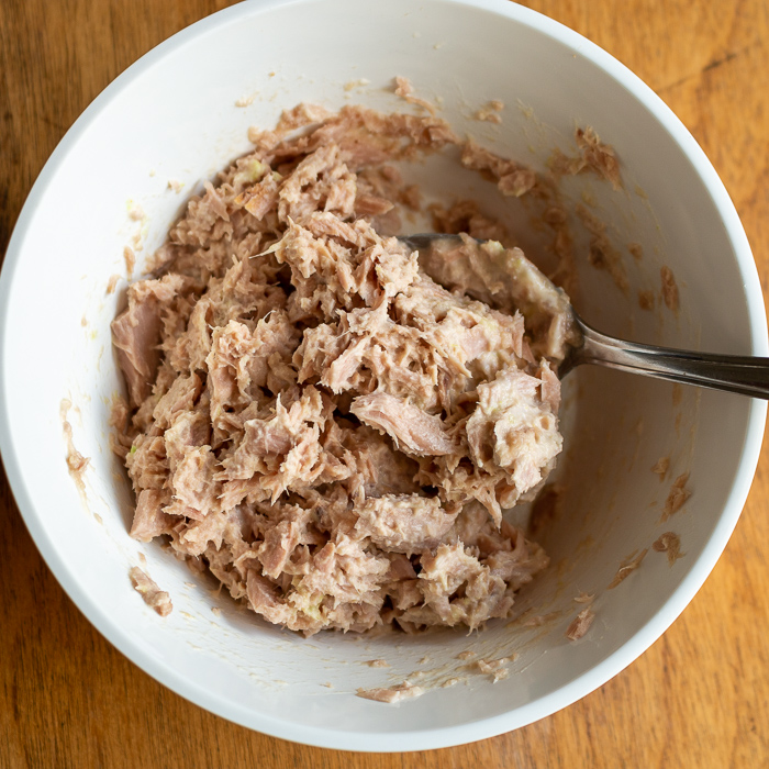 Tuna fish mixed with mayonnaise and wasabi in a white bowl.
