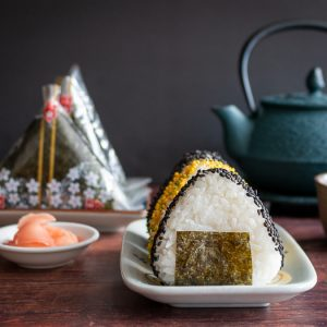 Onigiri served 2 ways one with sprinkles and one in wrappers with a side of hot green tea.