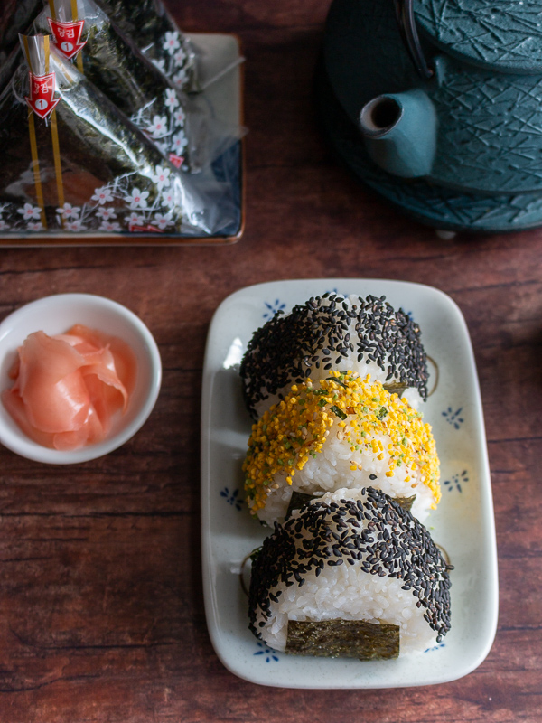 Top down photo of 3 onigiri with 2 with black sesame sprinkles and one with tomago (egg) sprinkles on top.