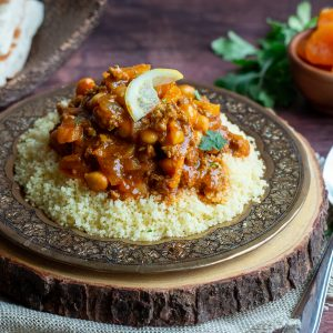 Moroccan Lamb Stew on a bed of couscous on a gold plate on top of a wooden board and garnish with lemon.