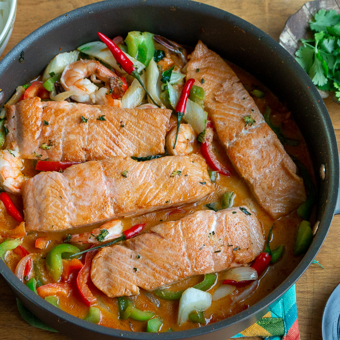 4 salmon fillets in a spicy Thai curry broth with vegetables in a black pan.
