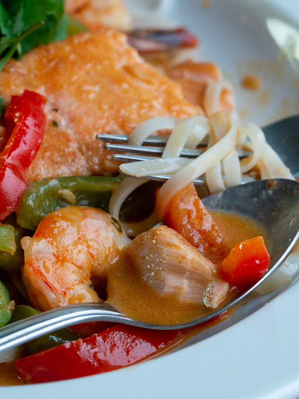Spoonful of succulent salmon with vegetables and the velvety delicious coconut broth.
