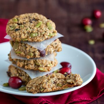 Cranberry Oatmeal Breakfast cookies stack with 4 on a white plate with one of them with a big bite out of it.