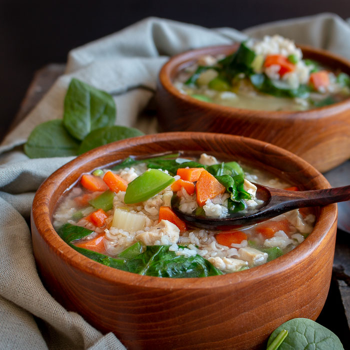 Immune Boosting Chicken and rice soup with veggies in a wooden bowl.