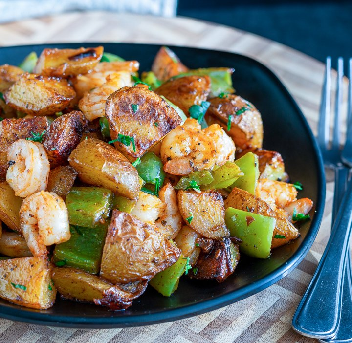 Piled in a black bowl is roasted crispy potatoes, green peppers, onions and shrimp.