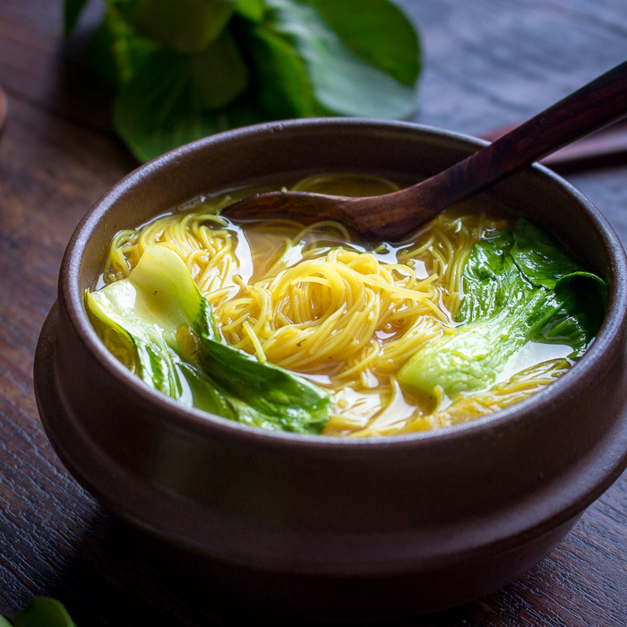 Golden Spiced Noodle Soup with bok choy in a brown soup bowl with soup spoon.