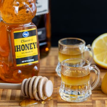 Ready for dosage with 2 Whiskey Honey Lemon Cough Syrup with a bottle of honey and whiskey and a half a lemon on a cutting board.