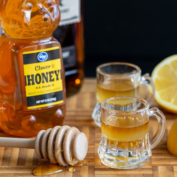 2 shots of Whiskey Honey Lemon Cough Syrup with a bottle of honey and whiskey and a half a lemon on a cutting board.