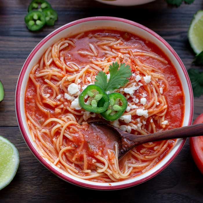 Mexican Noodle Soup garnished with cheese and cilantro.