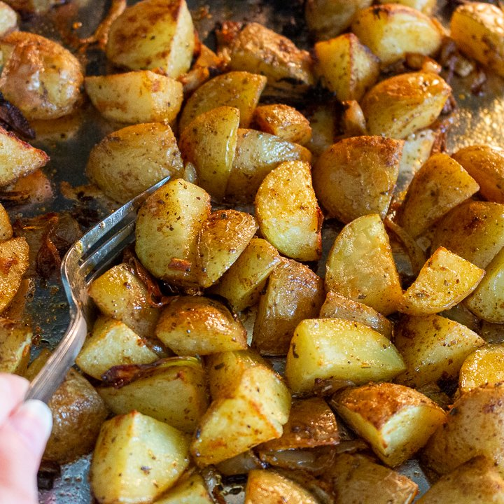 Potatoes getting tossed on the sheet pan part way through the roasting process.