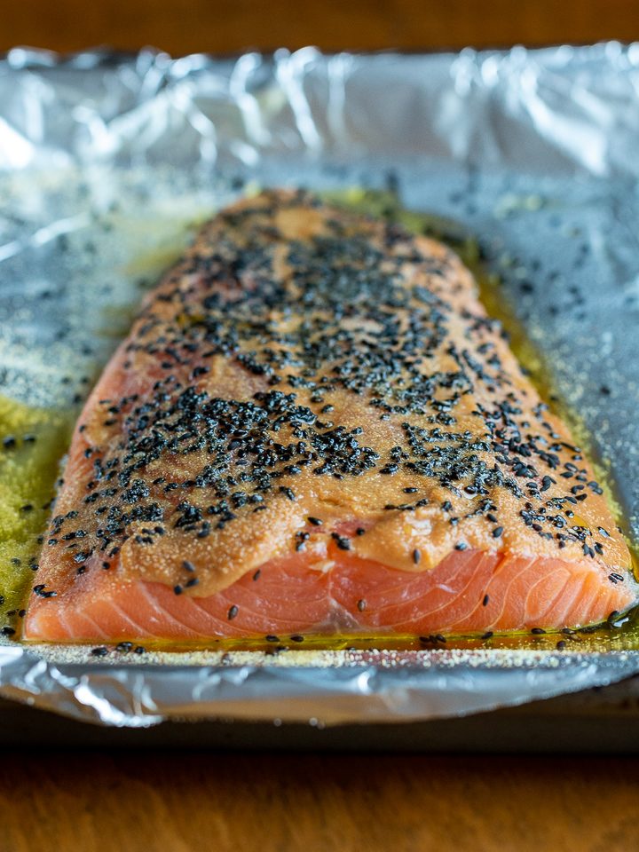 Salmon on a line sheet pan just slatethered in miso , black sesame seeds and olive oil, ready for the oven.