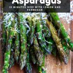 Best Grilled Asparagus on a wooden board dusted with fresh lemon zest and grated parmesan.