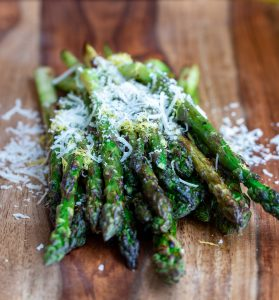 Grilled asparagus on a wooden board with lemon and parmesan.