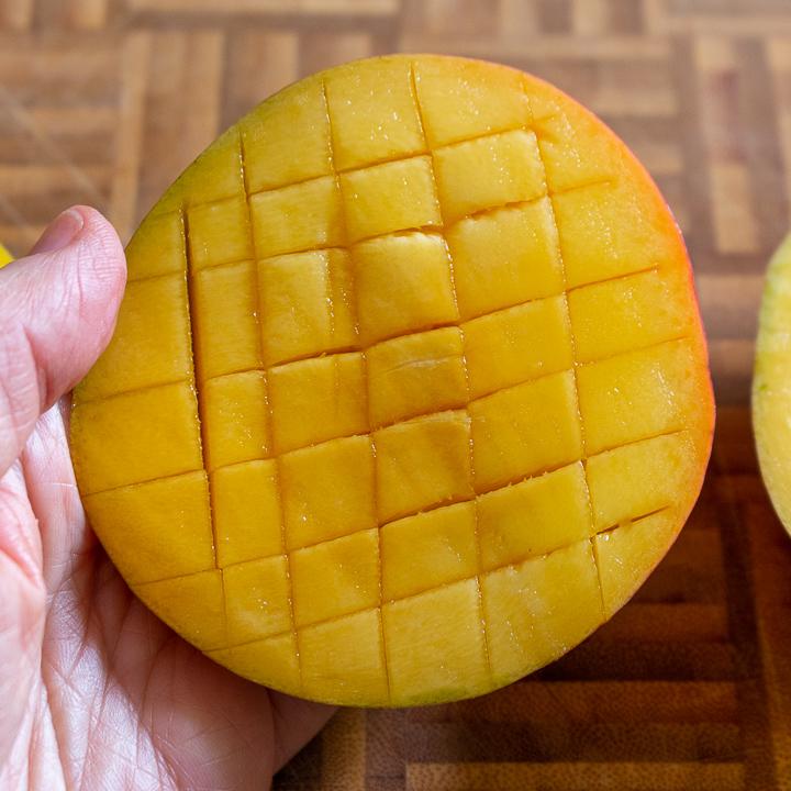 Crisscross cuts on mango half.