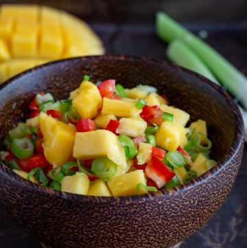 Wooden bowl of delicious fresh mango salsa with a half a a mango slice and green onion on the side.