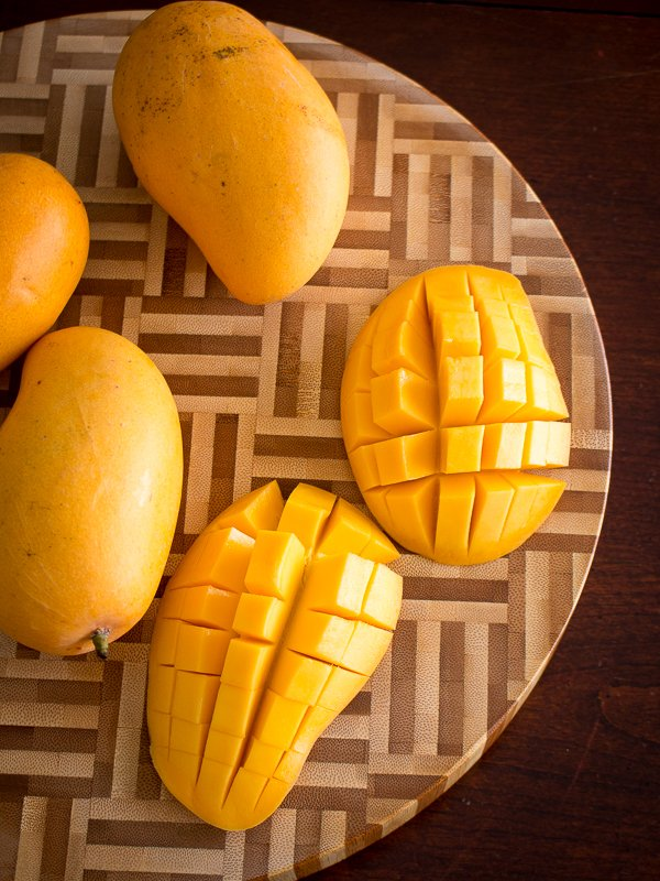 Mangoes slices and checkerboard sliced on a wooden cutting board.