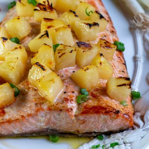 Baked whole salmon with toasty pineapple chunks on a white plate, garnished with green onions.