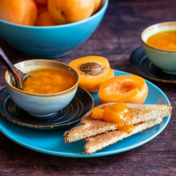 Toast slathered in apricot freezer jam with a bowl of jam next to it and fresh apricots in the background on a turquoise plate.