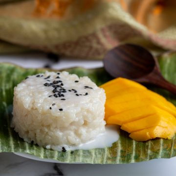 Mango Sticky rice on a banana leaf with a wooden spoon on the side and sprinkled with black sesame seeds.