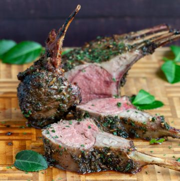 Whole Herb Marinated Grilled Rack of Lamb cut into slices on a cutting board with fresh herbs.