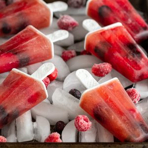 Rainbow Berry Rooibos Ice Pops on a sheet pan with ice and frozen mixed berries.