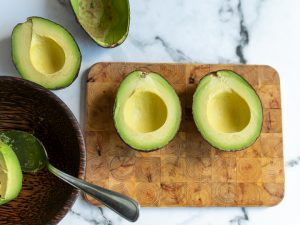 Avocados cut in half on a cutting board.