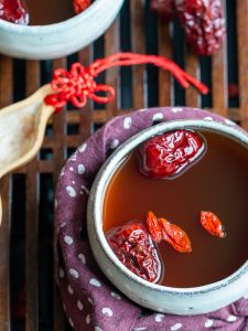 Delicious cup of Goji Berry and Red Dates Herbal tea in white tea cup garnished with extra dates on a Chinese Tea table.