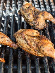 Cornish hens grilling skin side up after getting flipped.