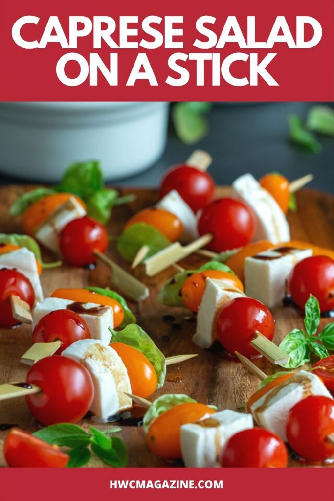 Caprese Salad on a stick drizzled with balsamic glaze on a wooden plate.
