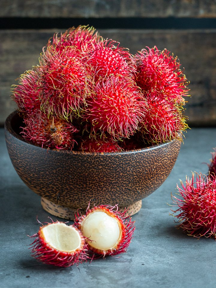 Large wooden bowl filled with fresh rambutan fruits and one is opened to show the snowy white fruit inside.