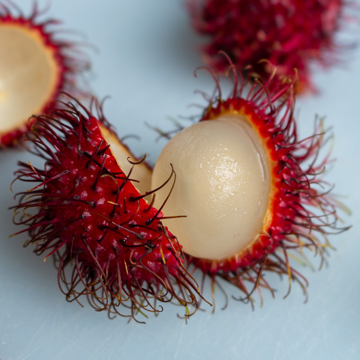 Rambutan fruit cut in half showing the white fruit inside.