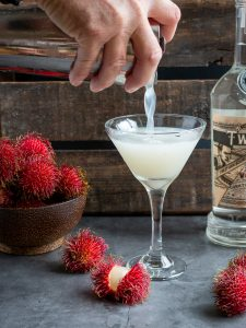 Vodka martini getting poured into a martini glass and rambutans around the table.