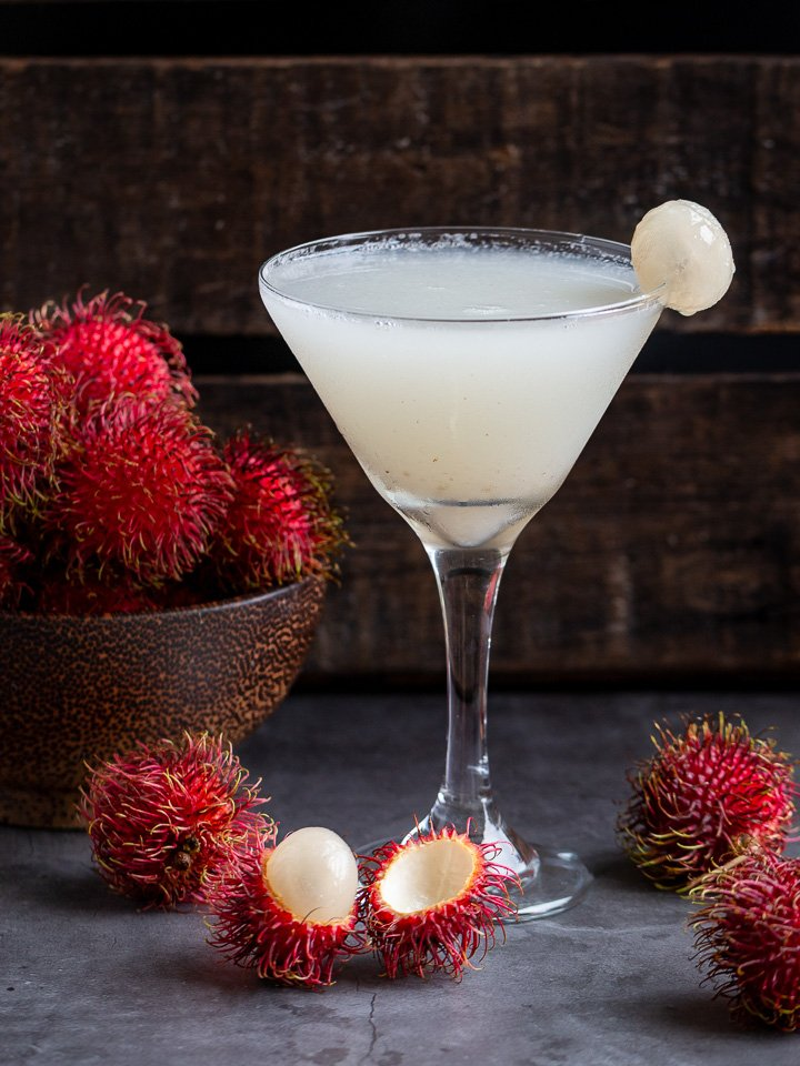 Snow flaky cold Rambutan Cocktail in a martini glass with a bowl of fresh rambutans in a wooden bowl.