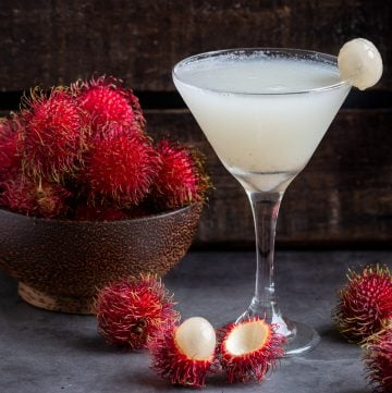 Icy cold Tropical Fruit Rambutan Cocktail in a martini glass with a bowl of fresh rambutans in a wooden bowl.