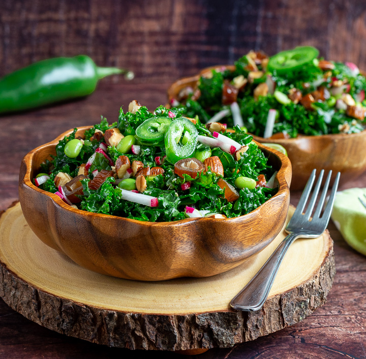 Two delicious bowls of Autumn kale salad in wooden bowls tossed with almonds and dates.